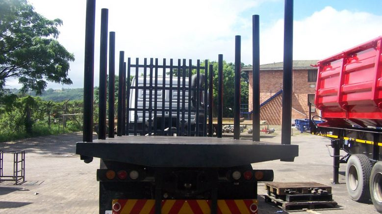 rear of rigid flatdeck truck with stake poles